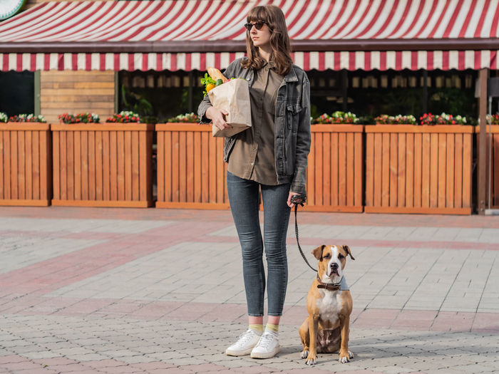 Shopping Adult Architecture Canine Casual Clothing Dog Domestic Domestic Animals Front View Full Length Groceries Looking Mammal One Animal One Person Pet Owner Pets Real People Standing Urban Warm Clothing