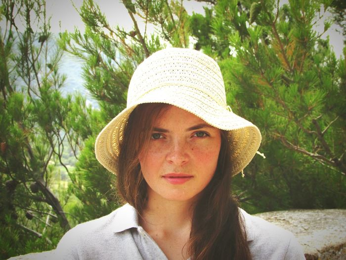 Portrait of young woman wearing hat against trees