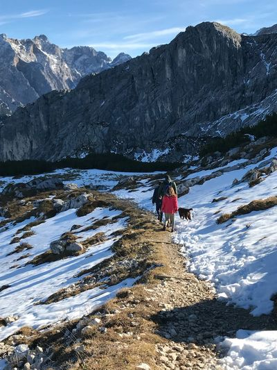 Rear view of people walking on snowcapped mountains
