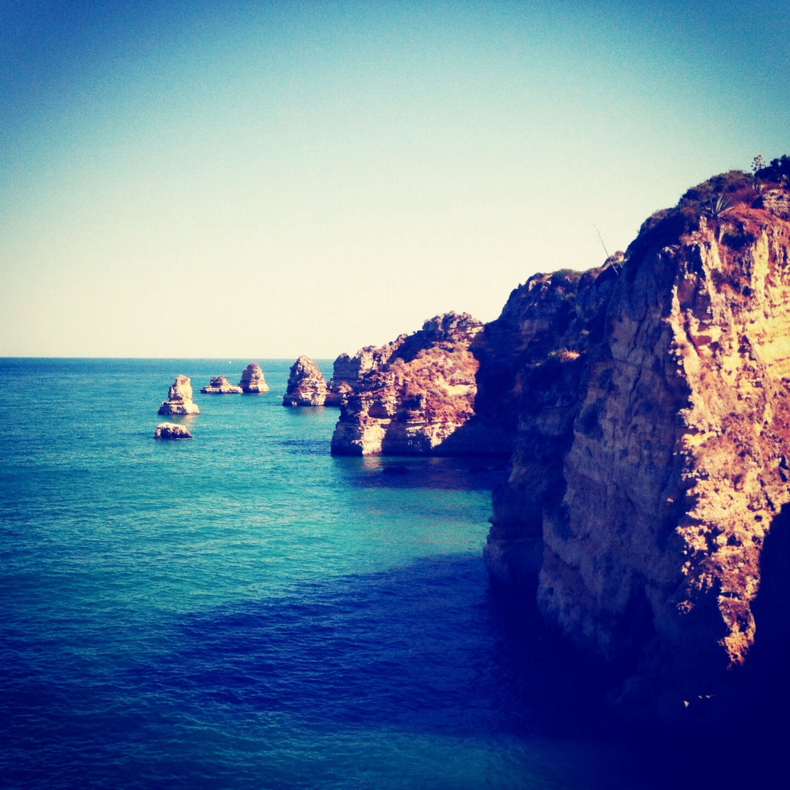 sea, water, clear sky, tranquility, tranquil scene, scenics, rock formation, rock - object, beauty in nature, copy space, horizon over water, blue, nature, cliff, waterfront, idyllic, rock, travel, sky, travel destinations
