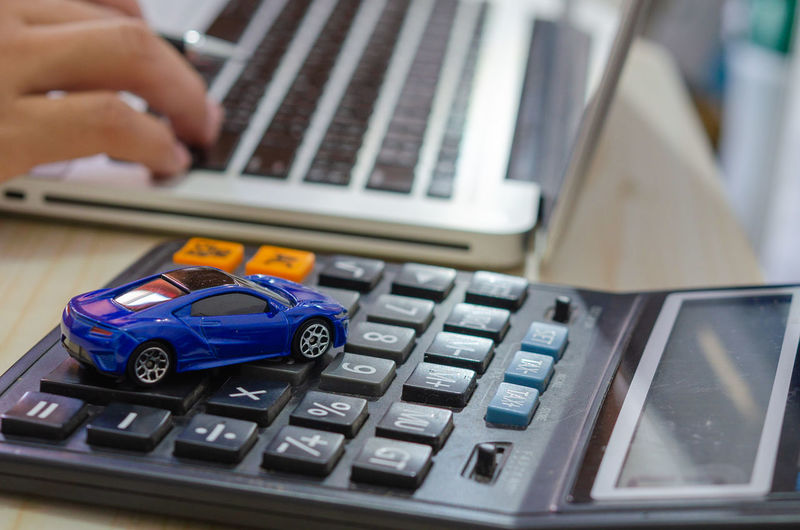 Close-up of toy car over calculator by person using laptop on table