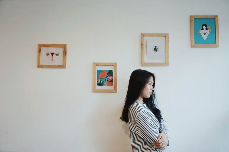 Woman standing against wall at home