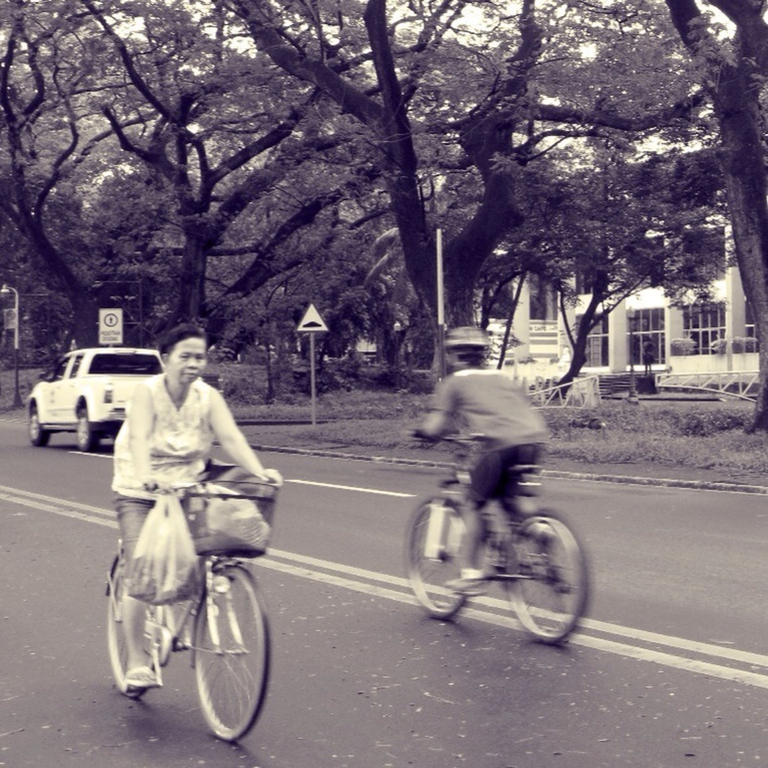 transportation, land vehicle, mode of transport, bicycle, street, tree, full length, riding, road, men, lifestyles, building exterior, car, cycling, city, on the move, leisure activity, walking