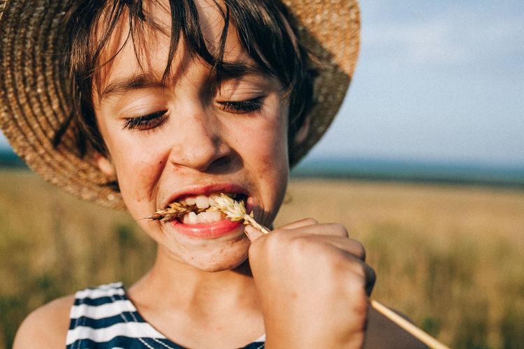 Close-up of boy eating crop at farm