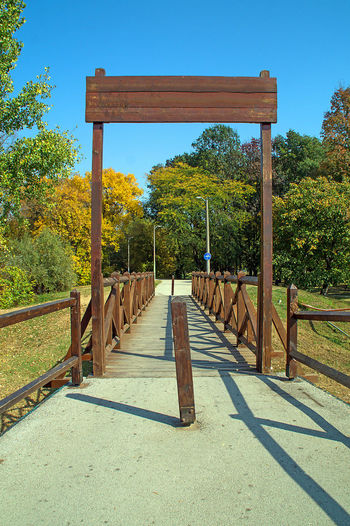 Small wooden bridge on park entrance Tree Nature Sunlight Tranquility No People Outdoors Park Relaxation Wood - Material The Way Forward Direction Bridge