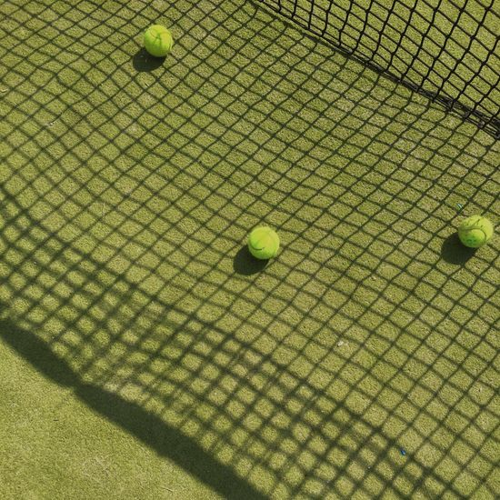 High angle view of tennis balls on grassy field in court