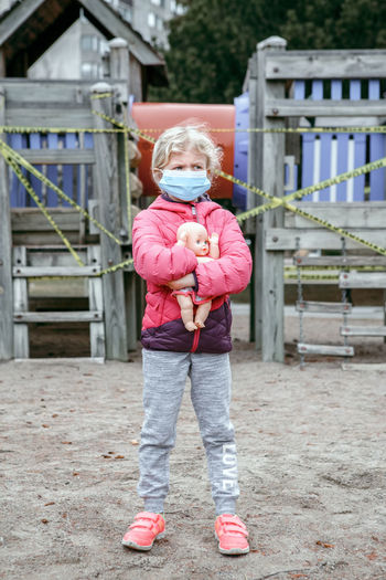 Girl wearing mask holding doll while standing at beach