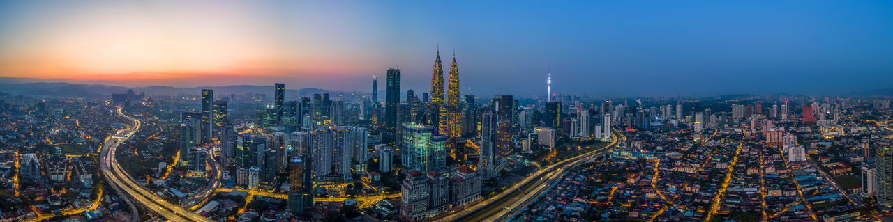 Panoramic view of modern buildings in city against sky during sunset
