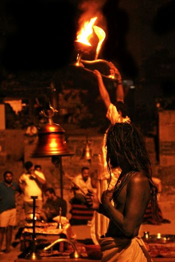 Rear view of woman standing by illuminated fire at night