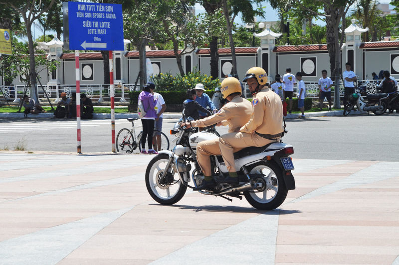 Traffic officers double up on motorcycle in Da Nang, Vietnam. Danang Helmets Law Enforcement Motorcycles Officers Partners Pillion Police Street Traffic Transport Transportation Uniforms Vietnam Working