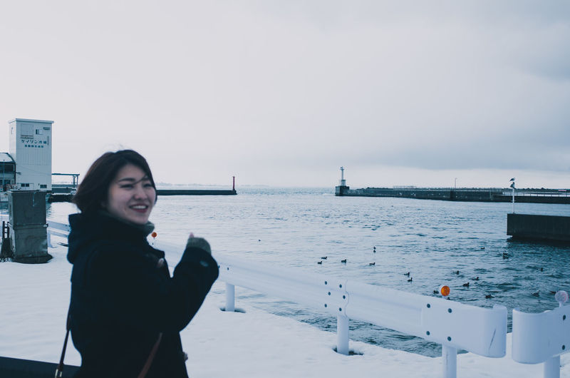 Portrait of young woman standing by sea against sky during winter