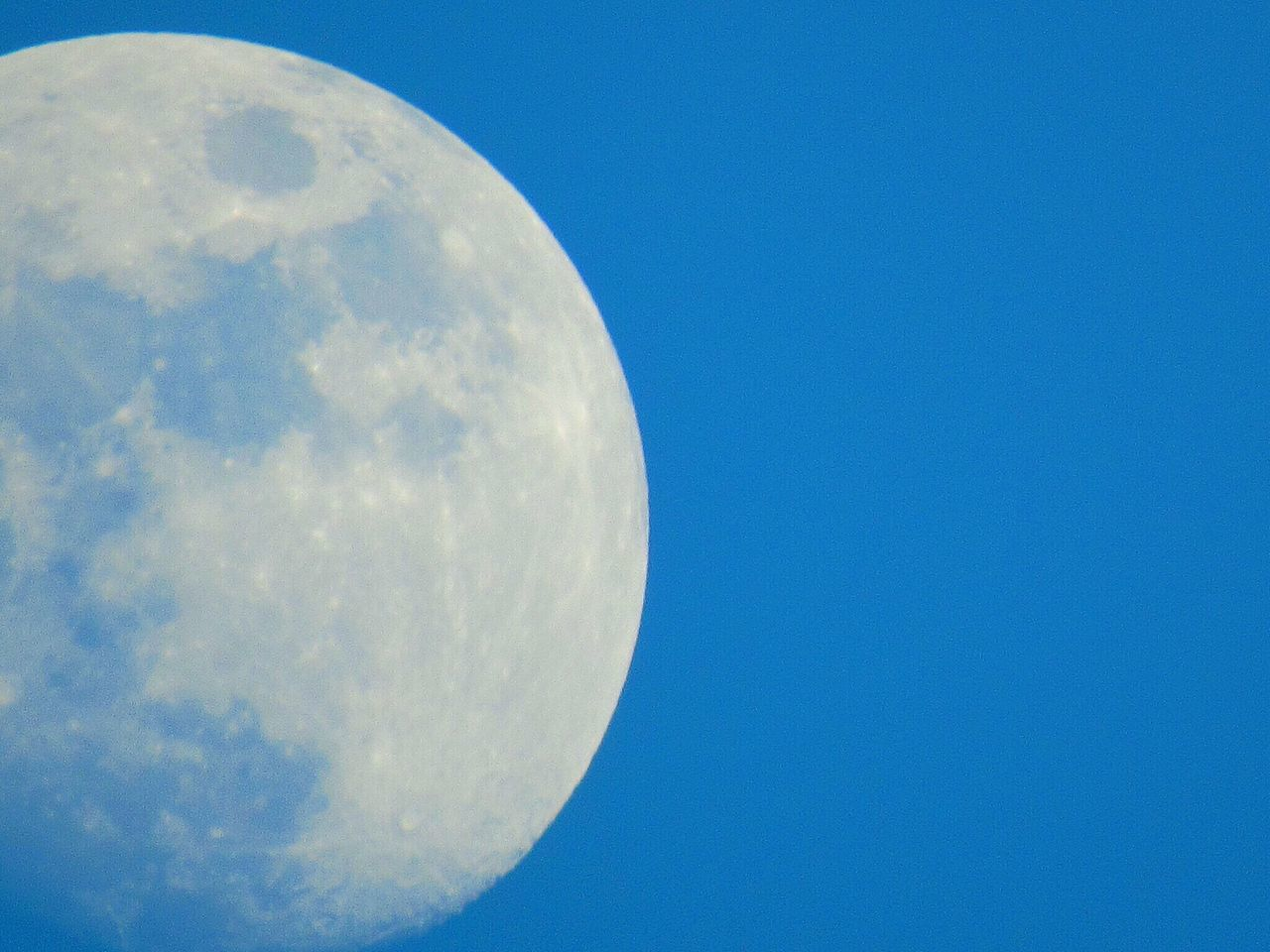 moon, circle, blue, low angle view, nature, moon surface, beauty in nature, astronomy, outdoors, no people, clear sky, semi-circle, sky, scenics, half moon, space, day, close-up