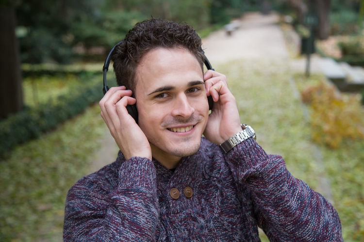 Cheerful young man standing and listening to music with headphones in autumn park. Nota al editor: Audio Autumn Casual Fun Happiness Headphones Lifestyle Listening Man Music Nature Cheerful Fall Forest Garden Handsome Joy Leaf Leisure Activity One Person Park Portrait Season  Smiling Young Adult