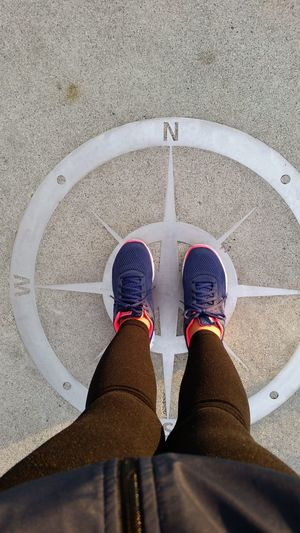 Woman standing on compass symbol on the ground