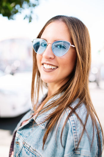 Portrait of smiling young woman wearing sunglasses