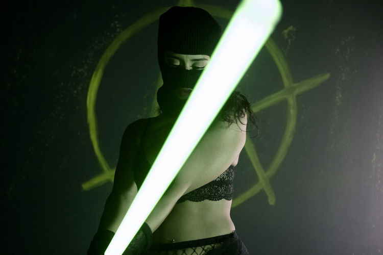 Close-up of masked woman holding a led light panel