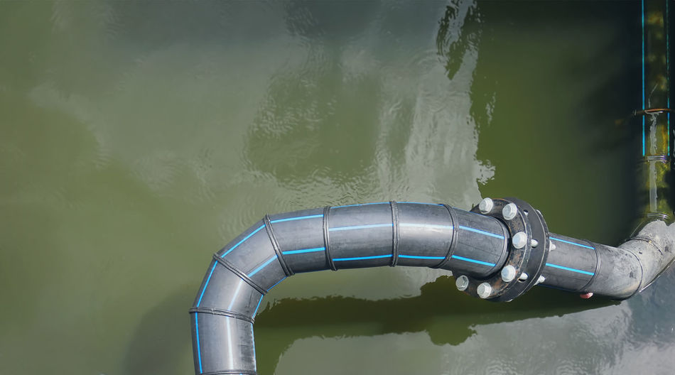 High angle view of black flexible hdpe pipes and bolted connection flange