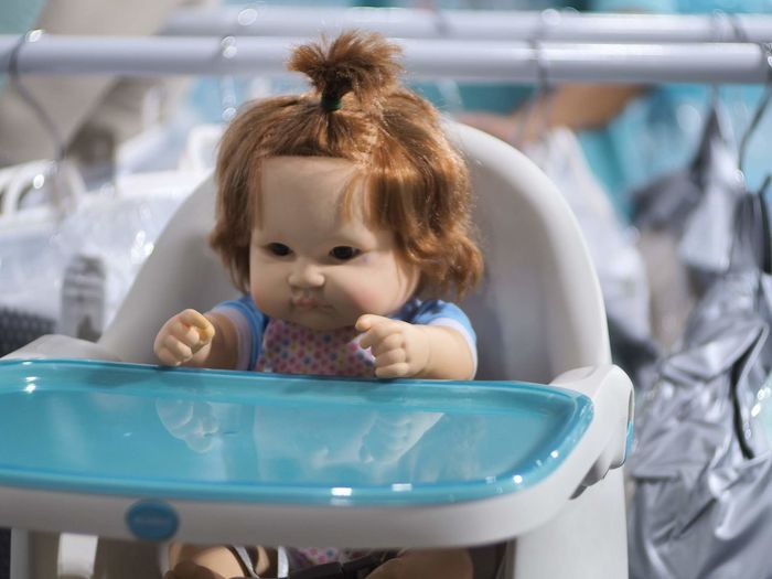 Close-up of cute doll on high chair
