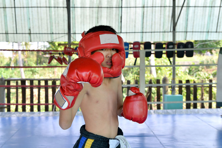 Portrait Of Teenage Boy Wearing Gloves While Standing In Boxing Ring