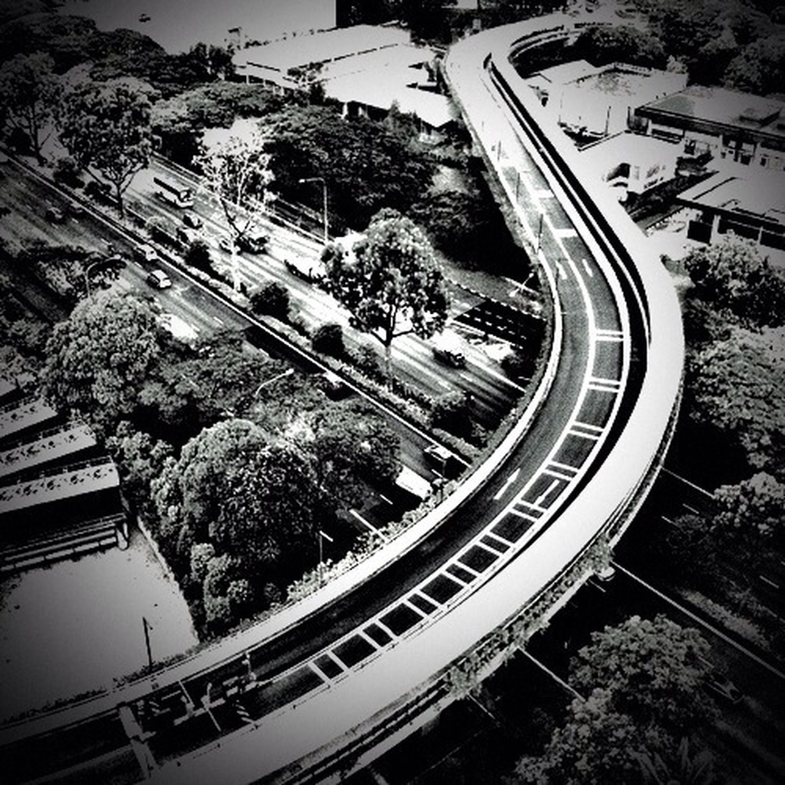 transportation, high angle view, tree, built structure, railroad track, mode of transport, architecture, road, land vehicle, city, building exterior, rail transportation, car, travel, public transportation, street, outdoors, elevated view, connection, incidental people