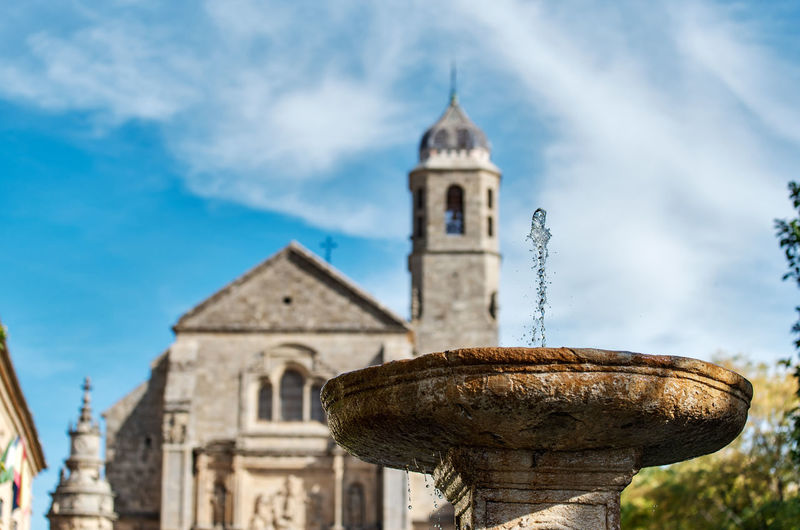Low angle view of drinking fountain against church