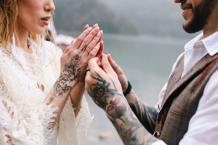 A man and a woman in love hold their tattooed hands and look at each other at the wedding