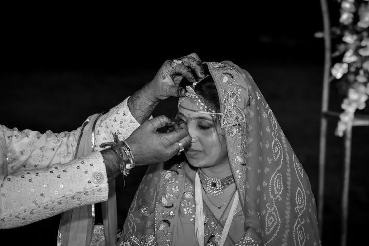 Midsection of couple were the groom puts sindoor on the hair  of his bride.