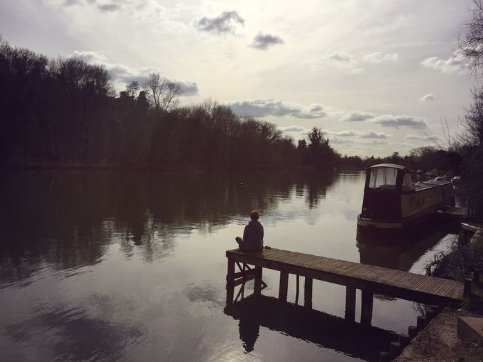 Rear view of woman sitting on pier over river