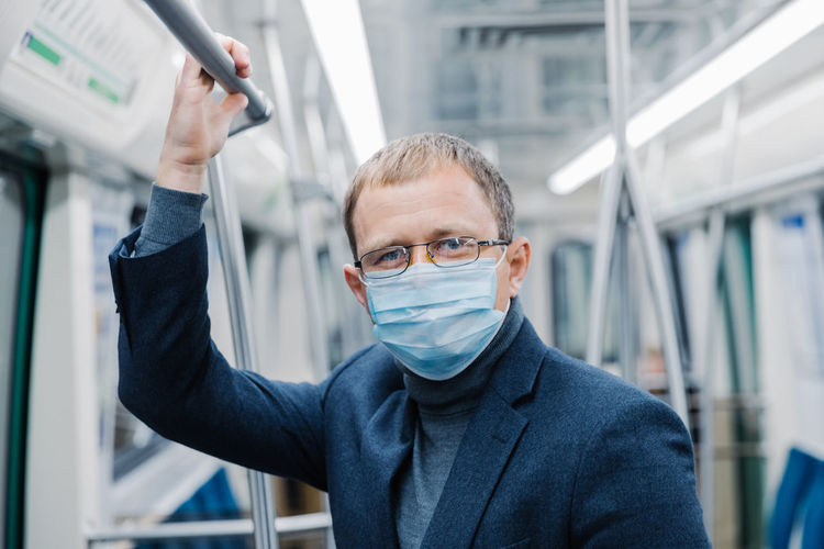 Portrait of businessman wearing mask in subway train