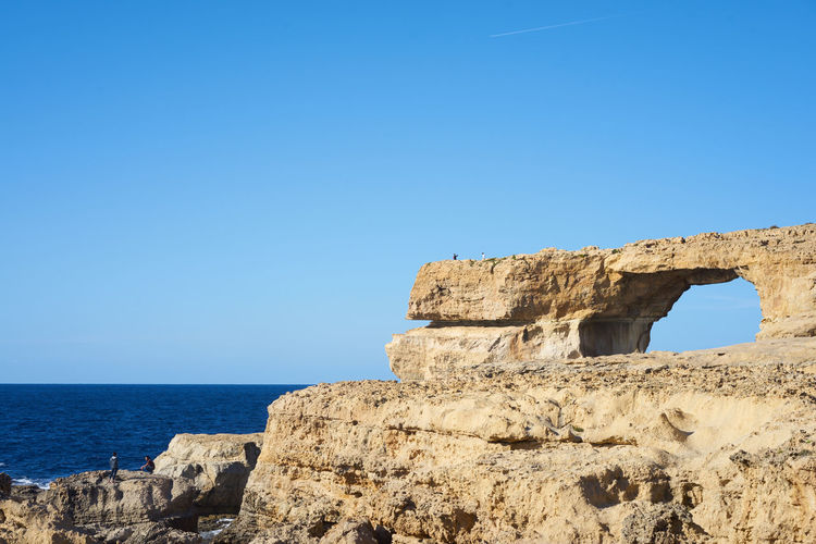 Cliff by sea against clear sky at gozo island