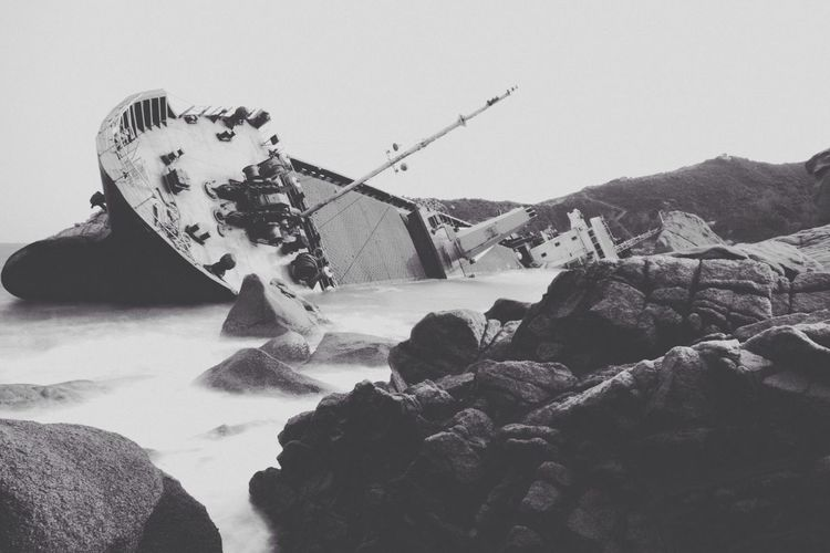 View of a sinking ship in water with rocks in foreground