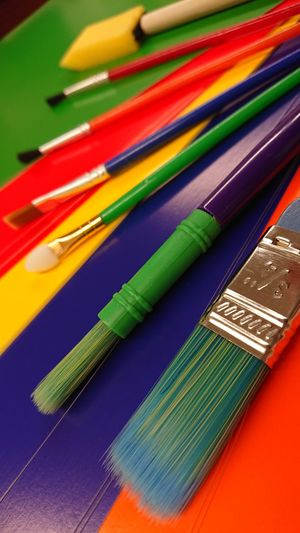 High Angle View Of Paintbrushes On Colorful Table