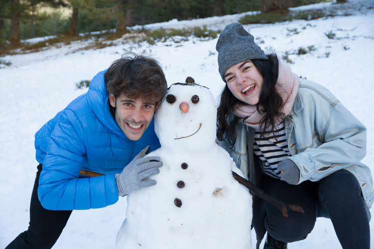 Portrait Of Young Couple With Snowman During Winter