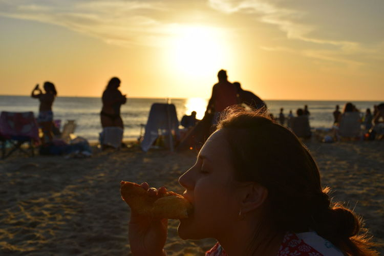 Close-Up Of Young Woman Eating Food At Beach During Sunset