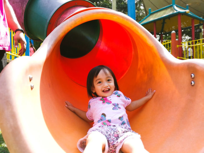 Portrait of cute girl playing on slide in playground