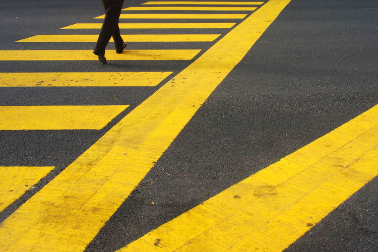 Low section of woman walking on zebra crossing