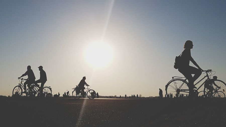 Silhouette People Riding Bicycles Against Sky