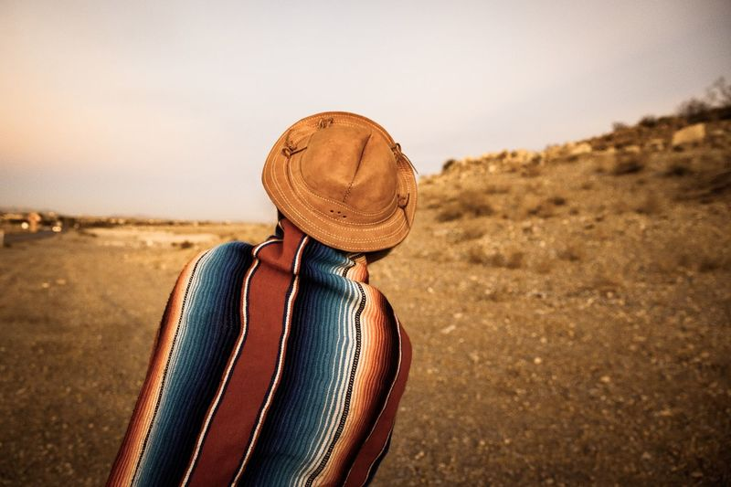 Hipster Traveler In Desert Of Southern Nevada, USA Standing Hipster Wanderlust Young Adult Girl Sepia Candid Horizontal Back USA Desert Travel Hat One Person Clothing Real People Lifestyles Women Leisure Activity Standing Adult Outdoors