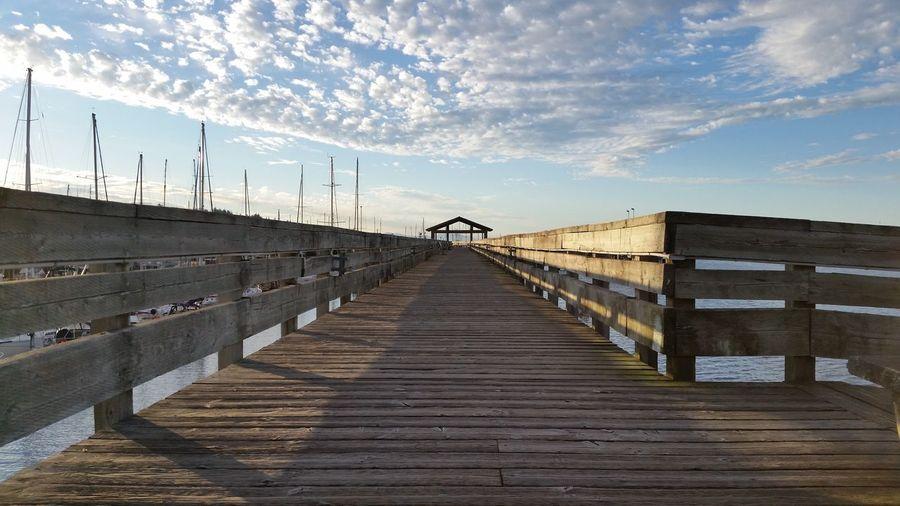 Pier against cloudy sky