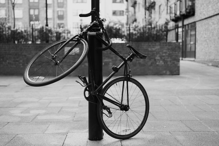 Bicycle parked on sidewalk by street against buildings