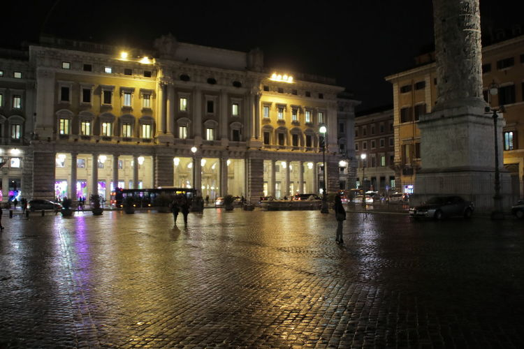 Illuminated buildings in city during rainy season at night