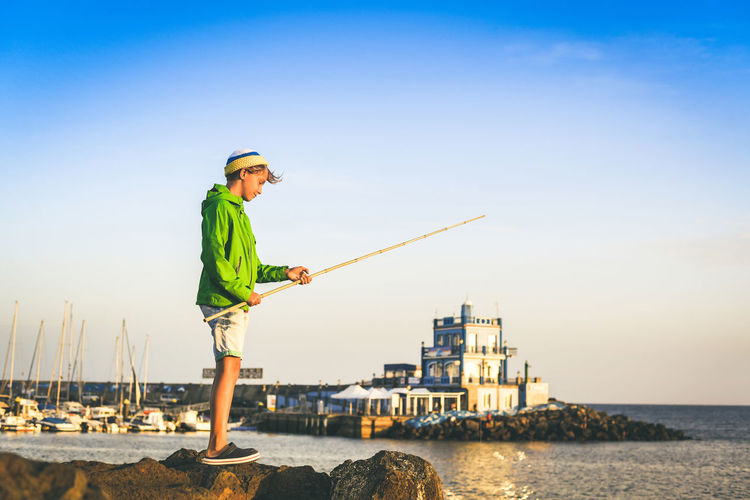 Boy fishing while standing by sea against sky