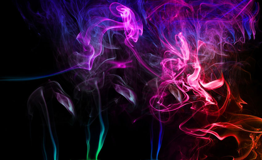 Close-Up Of Colorful Smoke Against Black Background