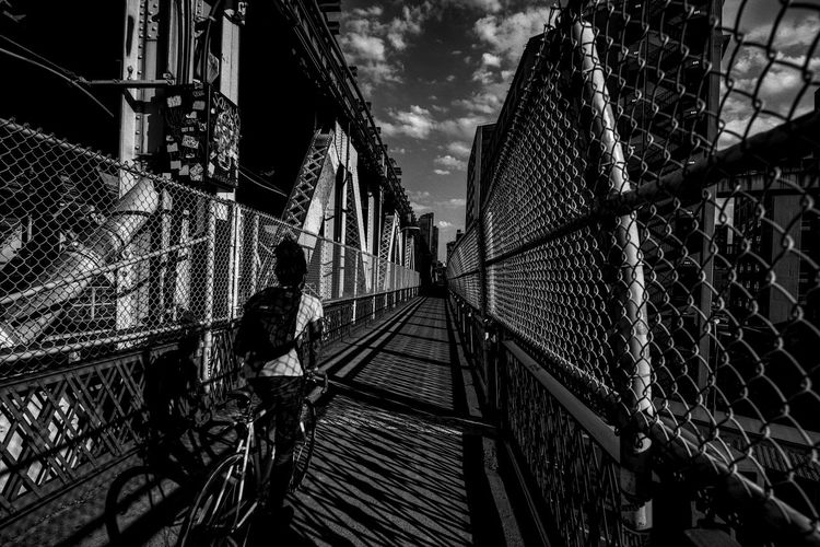 Manhattan Bridge Photographyisthemuse Built Structure Architecture Fence Bridge Real People Chainlink Fence Connection Bridge - Man Made Structure Building Exterior Transportation Men Sky Protection Safety City Metal Lifestyles Footbridge Outdoors Cycling Black And White