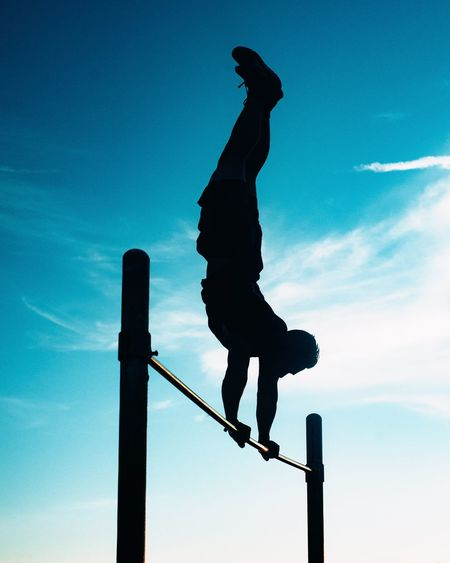 Low angle view of silhouette man on pole against sky