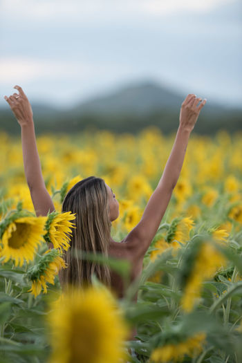 Yellow Flower Flowering Plant Plant Real People Land Women One Person Beauty In Nature Young Women Freshness Young Adult Arms Raised Hair Outdoors Hairstyle Human Limb Freedom Freshness Alive  Free Spirit