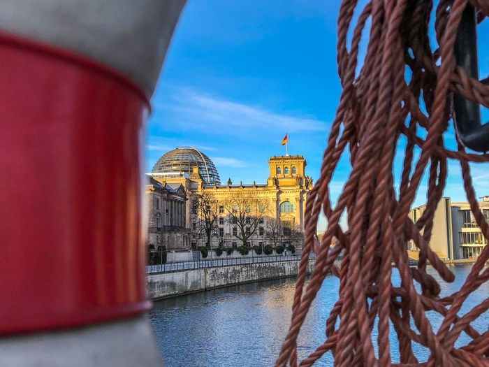 Reichstag Reflection Rettungsring Capitol Berlin Reichstag Blue Architecture Built Structure Connection Building Exterior Day Bridge - Man Made Structure History No People Water Outdoors Travel Destinations Red Sky