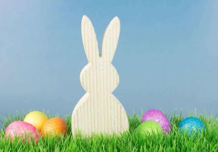 Close Up Of Colorful Easter Eggs With Decoration On Grass Against Wall