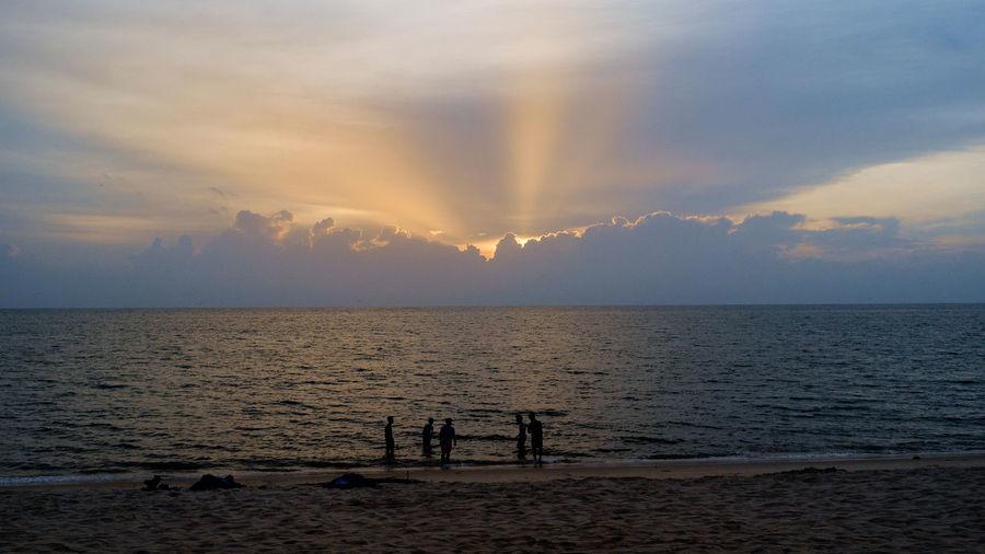 Men On Shore At Beach Against Sky During Sunset