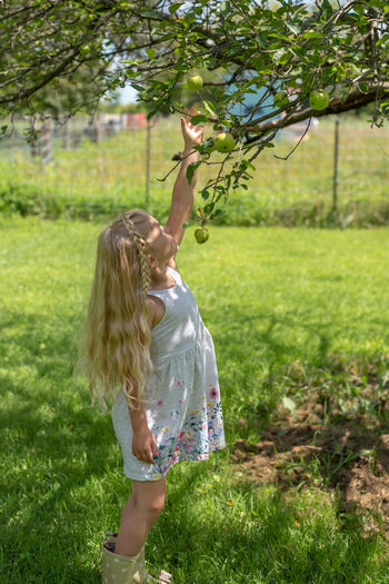 Girl standing by tree on field
